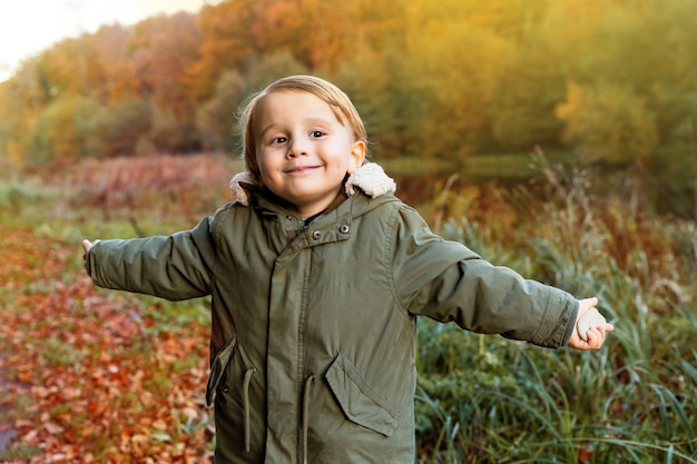 Szczęśliwy mały chłopiec spaceru w pięknym jesiennym parku. zabawny maluch spędza jesienny weekend w lesie o zachodzie słońca. zdrowy wypoczynek.