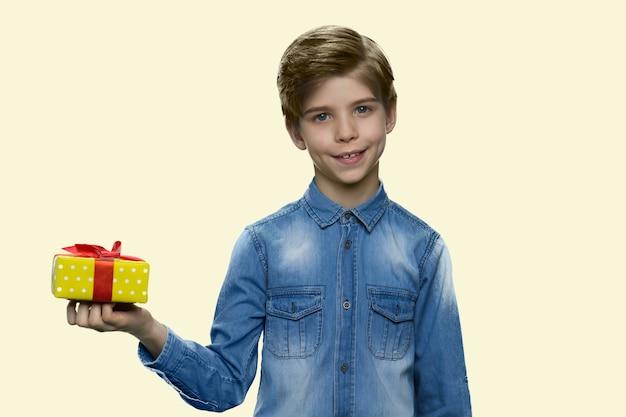 Szczęśliwy mały chłopiec trzyma małe pudełko na prezent