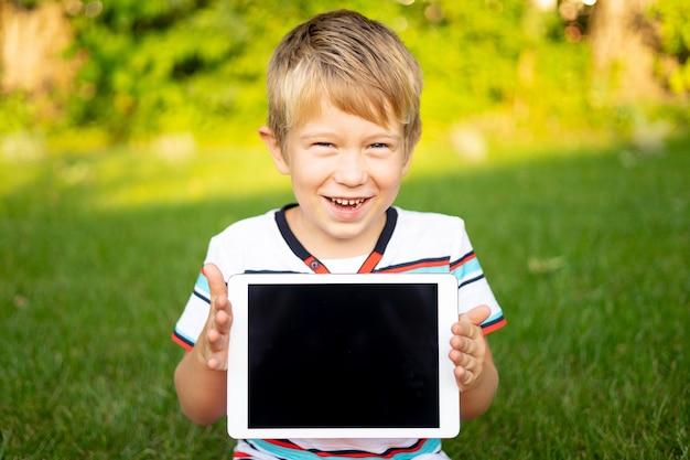 Szczęśliwy mały chłopiec trzyma tablet na zewnątrz w letnim parku