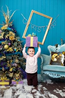 Szczęśliwy mały chłopiec uśmiechający się trzyma pudełko świąteczne.