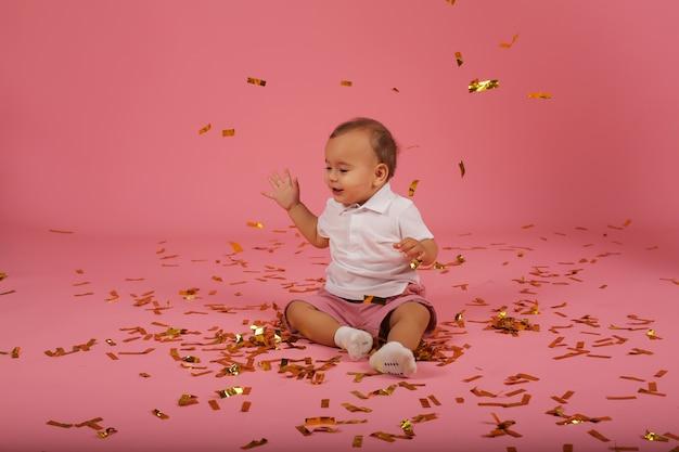Szczęśliwy mały chłopiec w białej koszulce i czerwonych spodenkach siedzi na różowym tle konfetti
