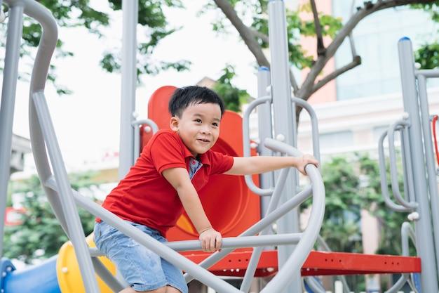 Szczęśliwy mały chłopiec wspinający się na plac zabaw dla dzieci