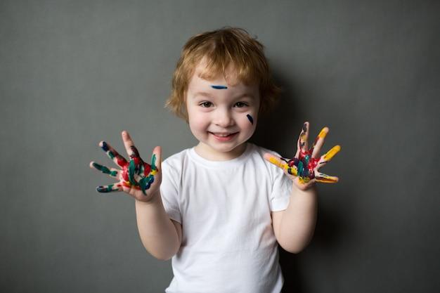 Szczęśliwy mały chłopiec z kolorowymi rękami, mały młody artysta
