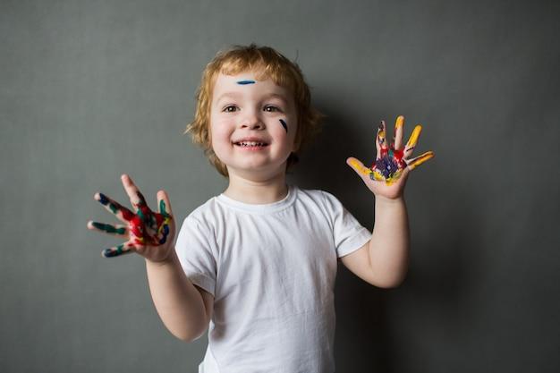 Szczęśliwy mały chłopiec z kolorowymi rękami, młody artysta