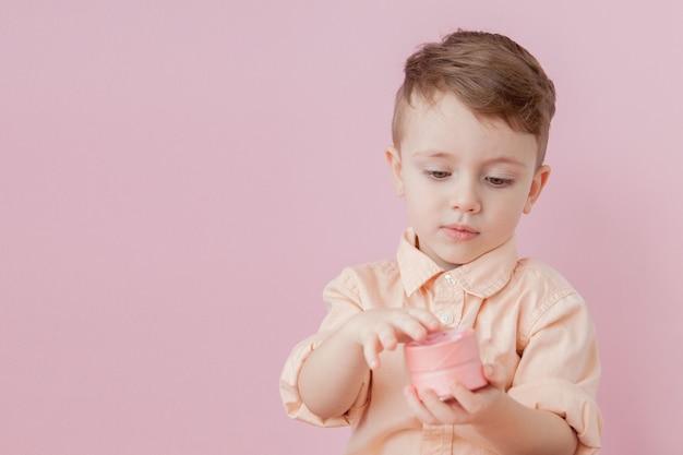Szczęśliwy mały chłopiec z prezentem. zdjęcie na różowo. uśmiechnięty chłopiec trzyma obecne pudełko. świąt i urodzin