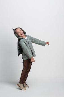Szczęśliwy mały chłopiec z rękami wyciągniętymi na białym tle, strzelanie w studio