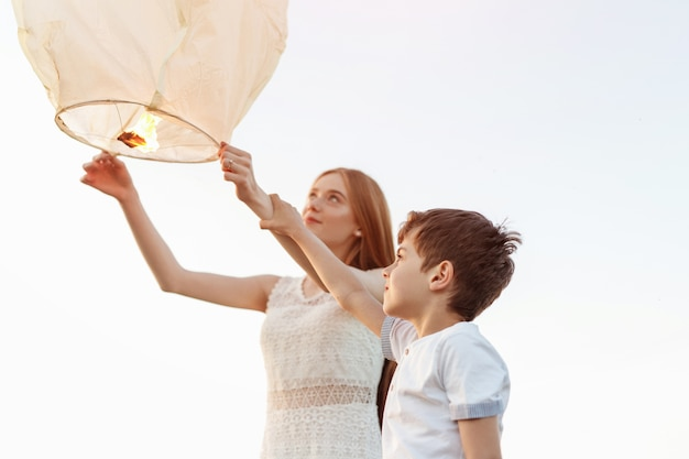 Szczęśliwy mały imbirowy chłopiec i dziewczynka razem puszczają latarnię