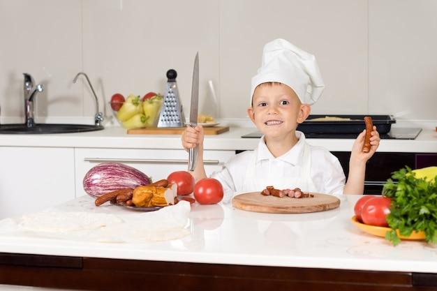 Szczęśliwy mały kucharz siekający składniki na białym drewnianym stole