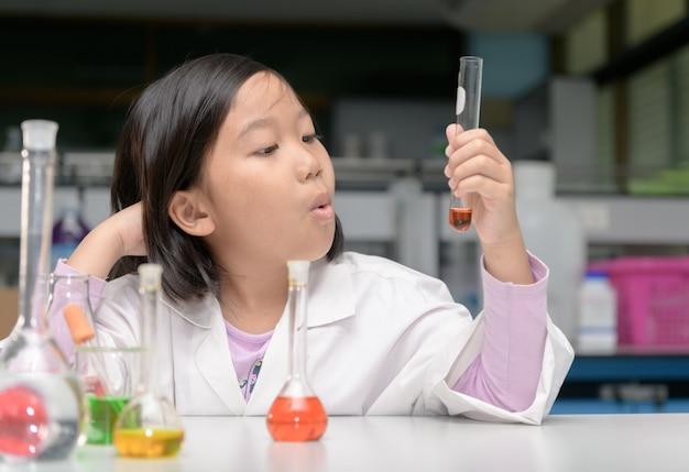 Szczęśliwy mały naukowiec w laboratorium płaszcz podejmowania eksperyment