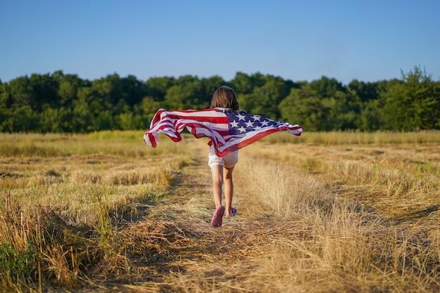 Szczęśliwy mały patriota dziewczyna działa w polu z amerykańską flagą.