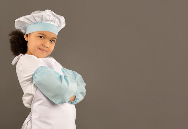 Szczęśliwy mały szef kuchni pozuje bocznego widok