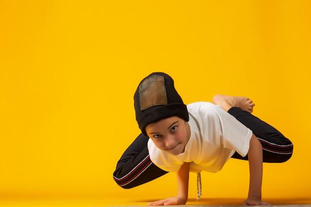 Szczęśliwy mały tancerz hip-hopu - chłopiec taniec na białym tle na żółtym tle. młody biały b-boy tańczy break dance.