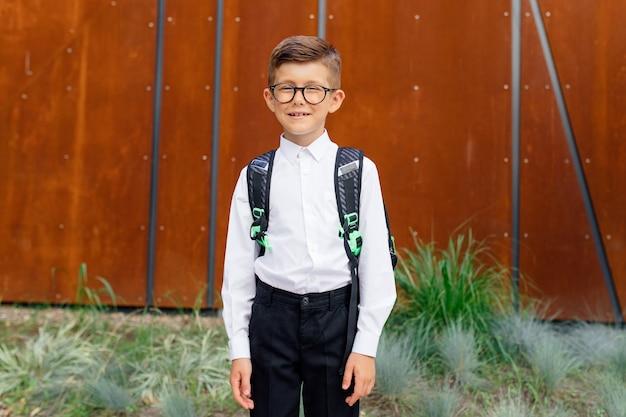 Szczęśliwy mały uczeń w okularach patrząc na kamerę na zewnątrz z powrotem do szkoły