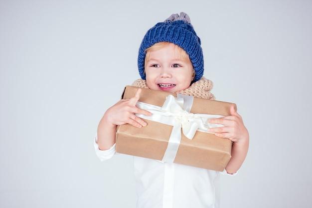 Szczęśliwy mały uśmiechnięty blond kręcone fryzury chłopiec w dzianym niebieskim kapeluszu z świątecznym pudełkiem z kokardą na białym tle w studio. prezent noworoczny w rękach dziecka płci męskiej