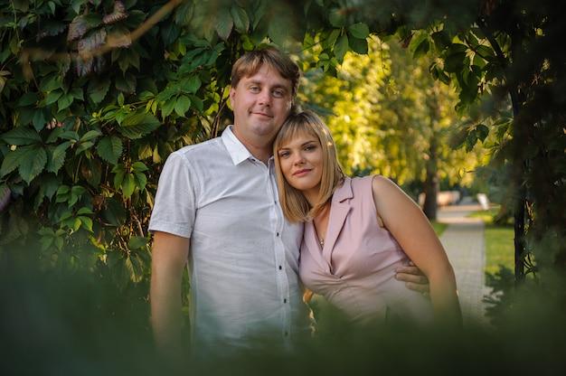 Szczęśliwy mąż i żona przytulanie w zielonym parku pod gałęziami drzew