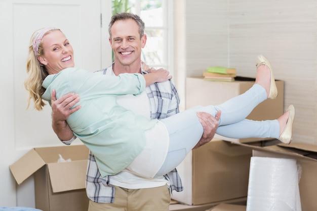 Szczęśliwy mąż niosący żonę w nowym domu