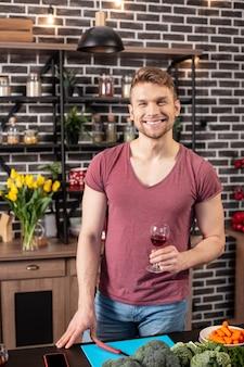 Szczęśliwy mąż. promienny, szczęśliwy, troskliwy mąż gotuje zdrowy obiad z warzywami i pije wino