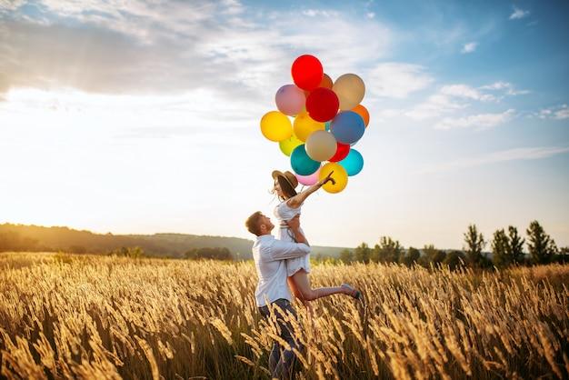 Szczęśliwy mąż przytula żonę z balonami w polu pszenicy. ładna para wypoczynku na letniej łące