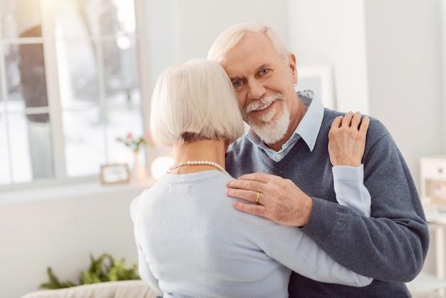 Szczęśliwy mąż. radosny starszy mężczyzna uśmiechający się tańcząc z ukochaną żoną, mocno ją przytulając