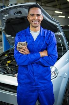 Szczęśliwy mechanik stoi w garażu naprawy