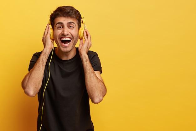 Szczęśliwy meloman męski cieszy się przyjemnym dźwiękiem nowych słuchawek, słucha ulubionej muzyki