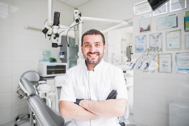 Szczęśliwy męski dentysta z fałdowymi rękami patrzeje kamerę