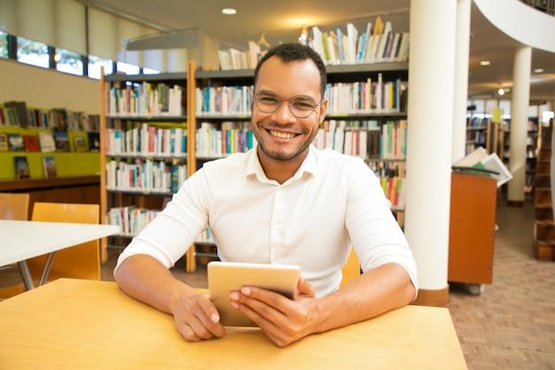Szczęśliwy męski klient używa publicznego hotspot wi-fi w bibliotece