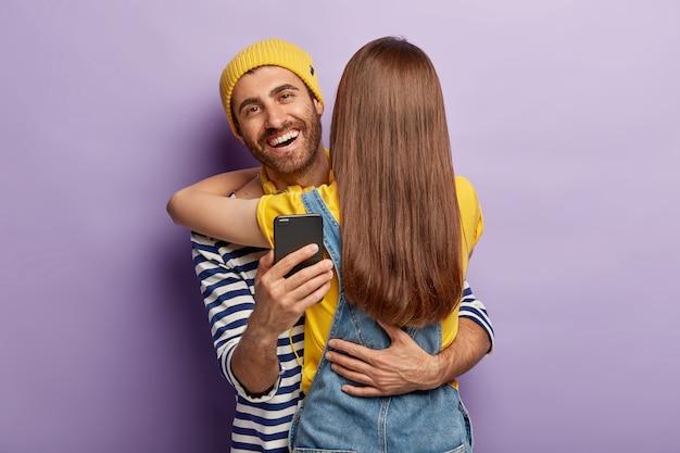 Szczęśliwy męski młodzieniec rozmawia przez internet w czasie z girlfrind, obejmuje kobietę, która stoi plecami do aparatu, cieszy się życiem, sprawdza wiadomości od obserwujących
