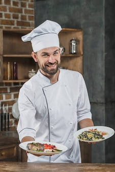 Szczęśliwy męski szef kuchni w białym mundurze oferuje wyśmienicie naczynia