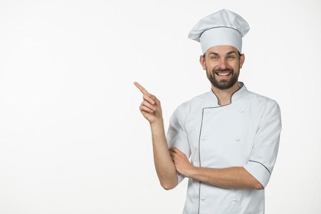 Szczęśliwy męski szef kuchni wskazuje jego palec przy coś odizolowywającym na białym tle