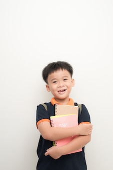 Szczęśliwy męski uczeń szkoły podstawowej trzymający książki
