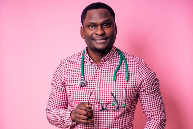 Szczęśliwy mężczyzna afryki chirurg medyczny kardiolog lekarz w białym fartuchu na różowym tle w studio.