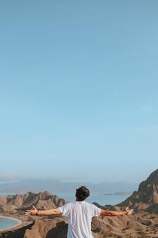 Szczęśliwy mężczyzna cieszący się widokiem na tle wzgórz i pejzażu morskiego z kopią miejsca na niebie