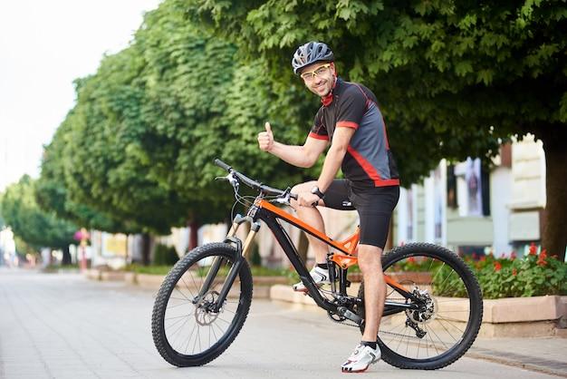Szczęśliwy mężczyzna cyklista w profesjonalnej kolarstwo odzieży i odzieży ochronnej pokazuje aprobaty siedzi na bicyklu przed zielonymi drzewami i ono uśmiecha się kamera. sportowiec zadowolony po porannym treningu