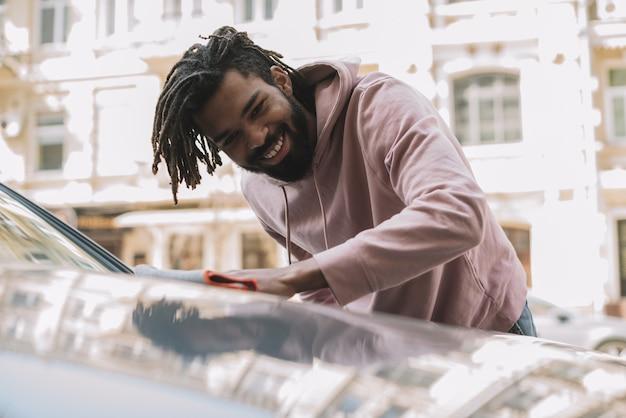 Szczęśliwy mężczyzna czyści samochodowego frontowego widok