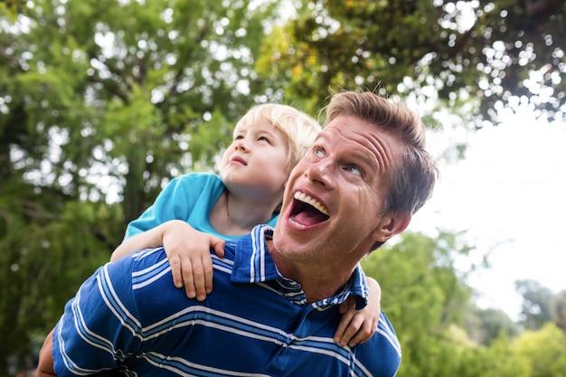 Szczęśliwy mężczyzna daje piggyback jego synowi