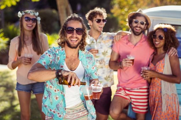 Szczęśliwy mężczyzna dolewania piwo w szkle podczas gdy jego przyjaciele stoi w tle