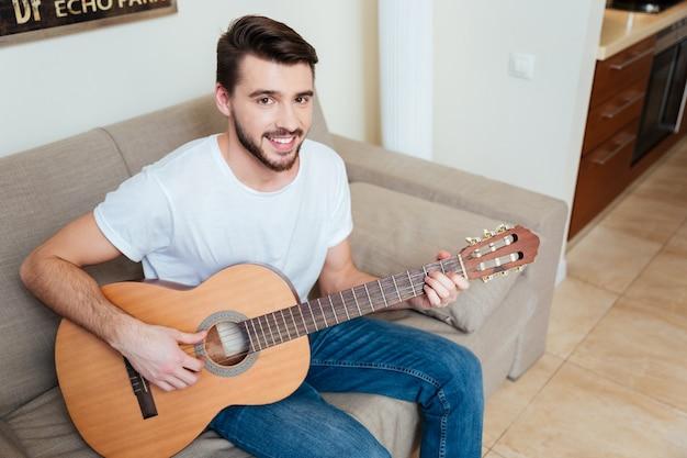 Szczęśliwy mężczyzna grający na gitarze na kanapie w domu