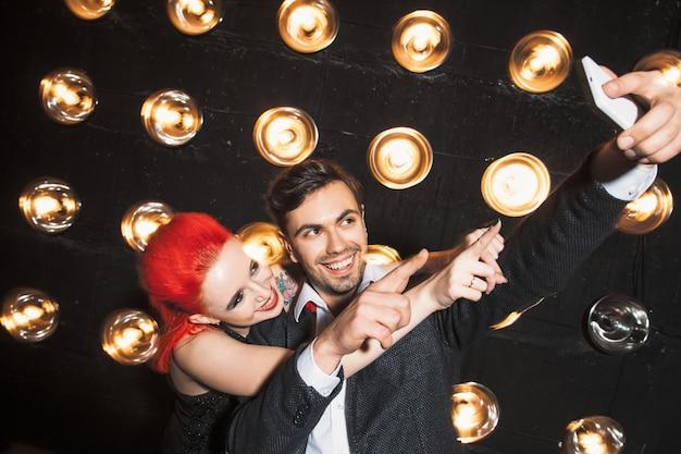 Szczęśliwy mężczyzna i kobieta na imprezie w klubie nocnym dokonywanie selfie