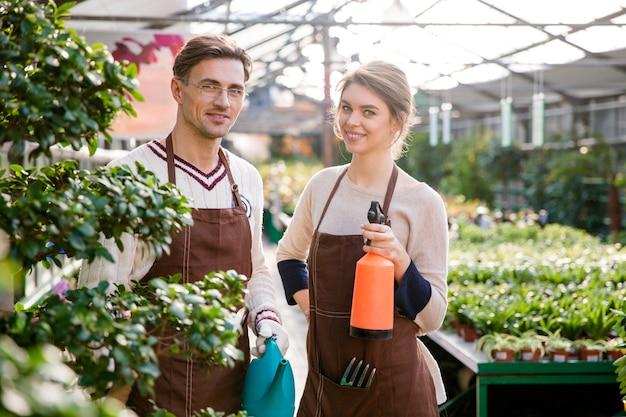 Szczęśliwy mężczyzna i kobieta ogrodnicy trzymający konewkę i pulweryzator do opryskiwania kwiatów i roślin w szklarni