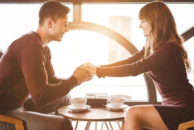 Szczęśliwy mężczyzna i kobieta siedzą przy stole w restauracji