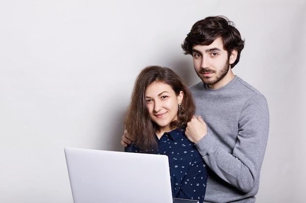 Szczęśliwy mężczyzna i kobieta stojąca bokiem z laptopem, patrząc bezpośrednio do aparatu izolowanych na białym. stylowy facet z brodą stojący za swoją dziewczyną lubiącą nowoczesne technologie.
