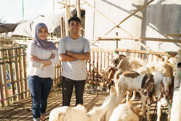 Szczęśliwy mężczyzna i kobieta stojąca w gospodarstwie. koncepcja poświęcenia eid adha