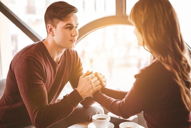Szczęśliwy mężczyzna i kobieta trzymają się za ręce przy stole w restauracji