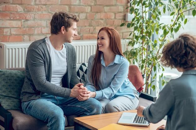 Szczęśliwy mężczyzna i kobieta trzymający się za ręce w biurze maklerskim