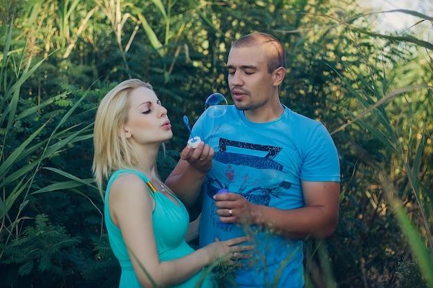 Szczęśliwy mężczyzna i kobieta w ciąży dmuchają bańki mydlane