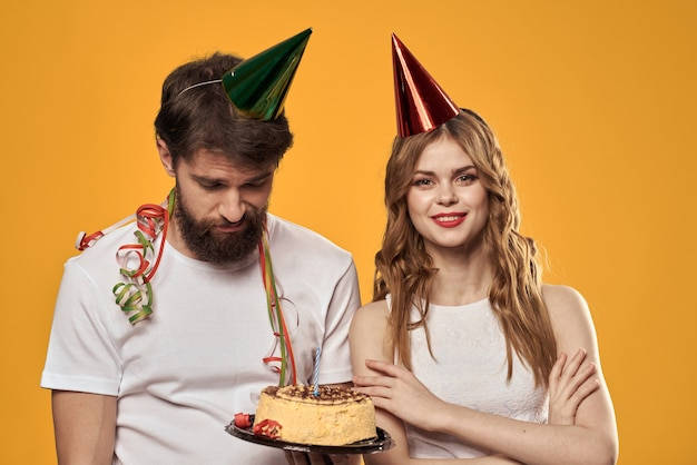Szczęśliwy mężczyzna i kobieta w czapce obchodzi urodziny na żółto