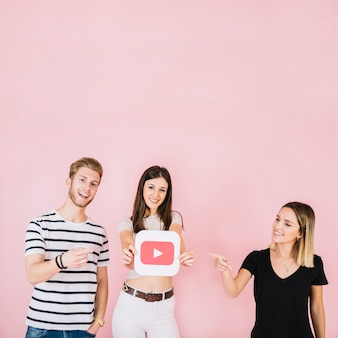 Szczęśliwy mężczyzna i kobieta, wskazując na ich przyjaciel wyświetlono youtube ikona