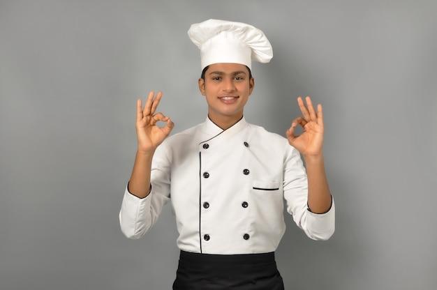 Szczęśliwy mężczyzna indyjski szef pokazujący gest ok jedną ręką nad szarym tłem zawód i koncepcja ludzi