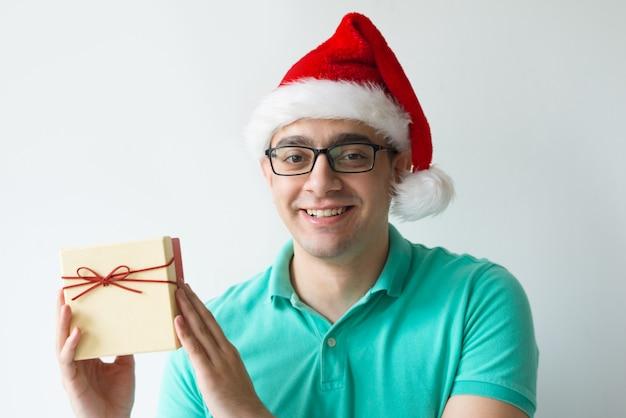 Szczęśliwy mężczyzna jest ubranym santa kapelusz i trzyma prezenta pudełko